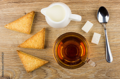 Zdjęcie XXL Płatkowate ciasteczka, mleko, herbata, cukier i łyżka na drewnianym stole