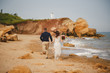 Outdoor beach wedding ceremony near the sea, stylish beautiful groom and bride are going to wedding altar on the sea shore