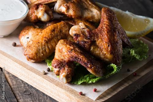 Plakat Zakończenie fotografia bbq kurczaków skrzydła z fries i piwem. Mięso z grilla z sosami, ketchupem, majonezem. Koncepcja fast and fast-food.