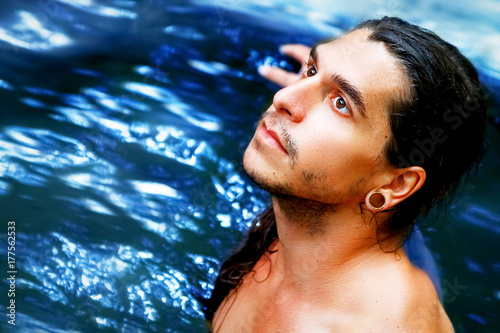 Photo  A handsome guy with long hair, brown eyes and piercings on a background of blue water