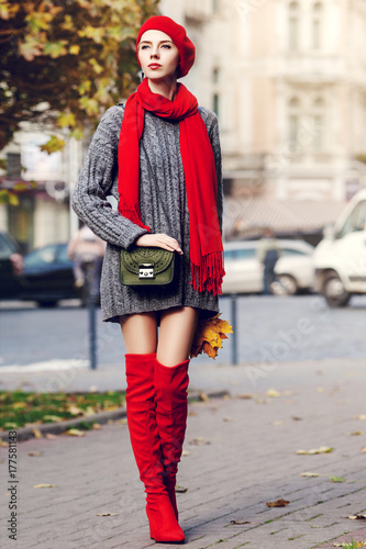 Fototapeta Outdoor full body portrait of young beautiful fashionable woman wearing trendy red high, over knee boots, stylish clothes and accessories. Model posing in street. Elegant autumn outfit. Female fashion obraz