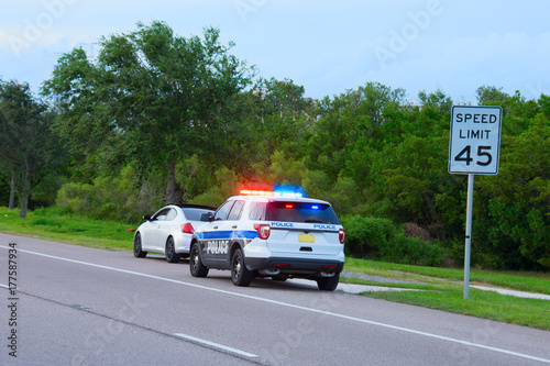 Cuadros en Lienzo Police truck suv vehicle with flashing red and blue lights has pulled over a sports car for speeding and they happen to be on the side of the road by a speed limit sign