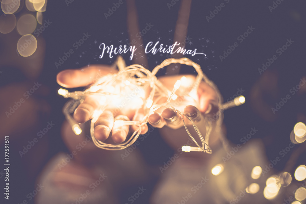 Fotografering  Merry christmas glowing word over hand with party light  string bokeh in vintage filter,Holiday, new year season
