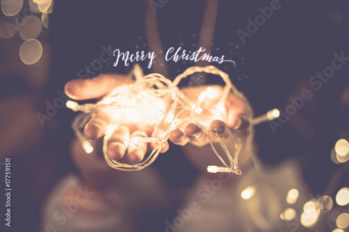 Obraz na plátně Merry christmas glowing word over hand with party light  string bokeh in vintage filter,Holiday, new year season