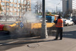 October 2017, Moscow, Russia, street the Warsaw highway. A worker in an orange vest like paper and dirt from roadside poles with a jet of water under pressure