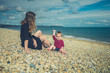 Young mother sitting on beach with her baby