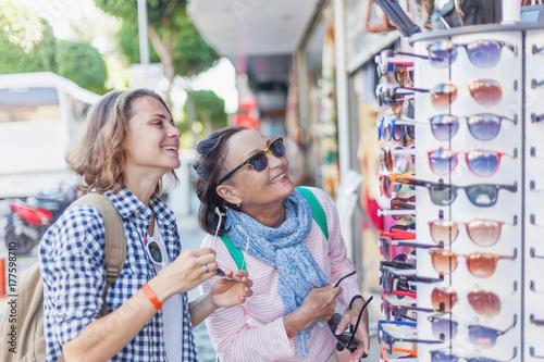 Plakat Stylowa i piękna dojrzała matka i dorosła córka podróżują razem, idą ulicą i przymierzają okulary. Rodzina, podróże, zakupy, radość, komunikacja