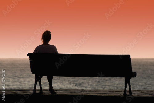 Leinwand Poster Silhouette of woman sitting alone on the bench in front of the sea