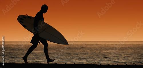 Plakat Sylwetka surfera odprowadzenie na plaży przy zmierzchem