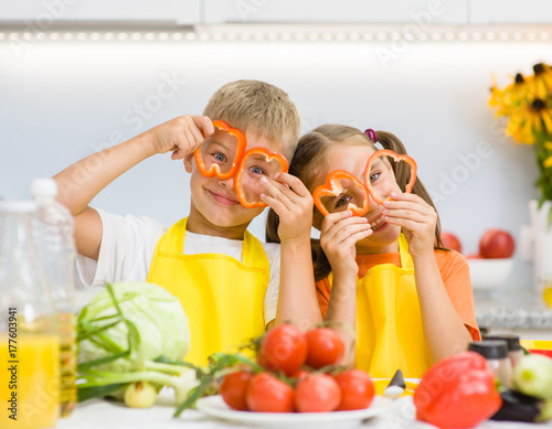 Happy kids having fun with food vegetables at kitchen holds pepper before his...
