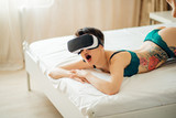 Sexy woman in underwear using VR glass in bed, virtual reality