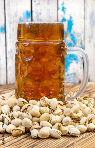 Plakat Szkło piwo z pistacjami na drewnianym stole.