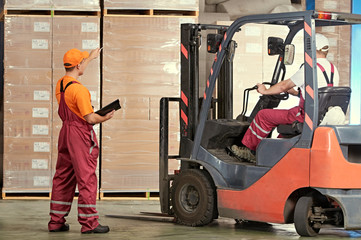 Warehousing and storage. warehouse workers works with forklift loader