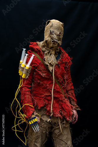 Fotografie, Obraz  An evil character at the Cosplay Festival, a bag on his head, a hanger and syringes as a weapon