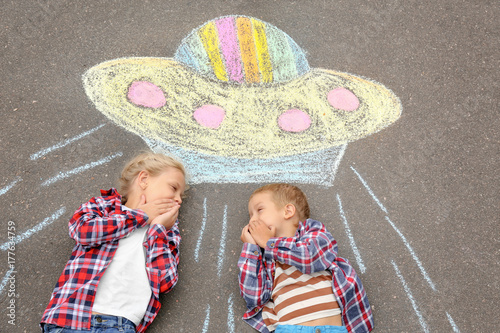 Poster UFO Little boy and girl lying near chalk drawing of alien spaceship on asphalt