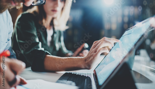 Woman pointing on digital tablet screen at night office .Horizontal.Blurred background.Flares.