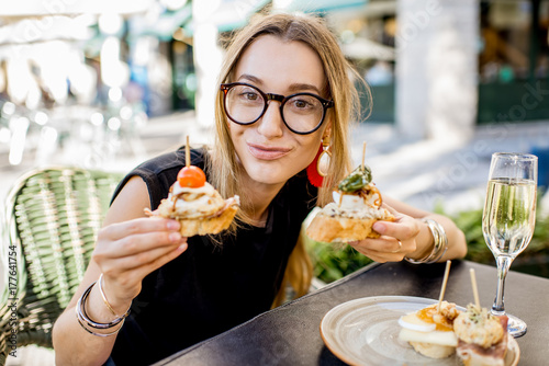 Fotografía  Young woman enjoying tasty appetizer with pinchos, traditional spanish snack, an