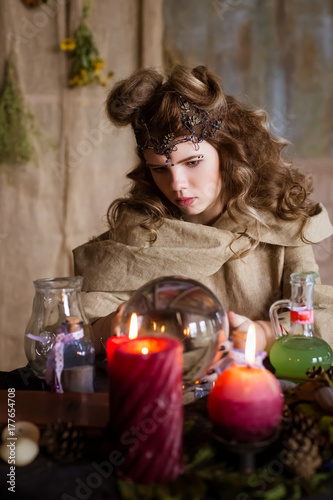Beautiful, cute teen girl, the witch looks into a crystal