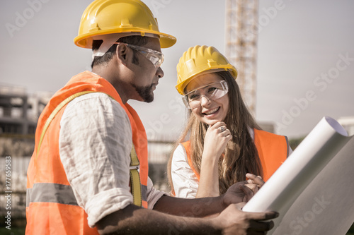 Valokuva civil engineers working at construction site wearing safety glasses, jacket and