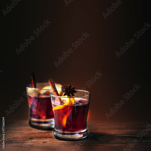 Zdjęcie XXL Gorący Rozmyślający wino dla zimy i bożych narodzeń na drewnianym tle z copyspace. Gorące wino z pomarańczowymi owocami i przyprawami
