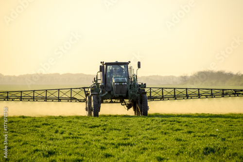 Tractor on the sunset background. Tractor with high wheels is making fertilizer on young wheat. The use of finely dispersed spray chemicals