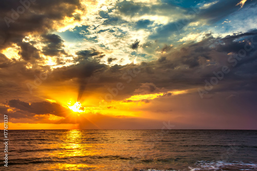 A bright colorful orange sun makes the rays through dense blue clouds on the Bali Sea. Sunset on the Lombok island, Indonesia.