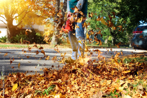 Photo Man working with  leaf blower: the leaves are being swirled up and down on a sun