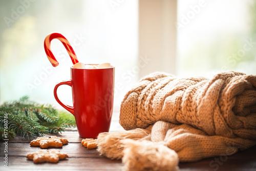 Zdjęcie XXL Bożenarodzeniowy miodownik, cukierek, kawa z marshmallows w czerwonej filiżance, trykotowy szalik, rożki i choinek gałąź na drewnianym stole na nadokiennym tle ,. Boże Narodzenie wakacje tło, zima przytulny dom