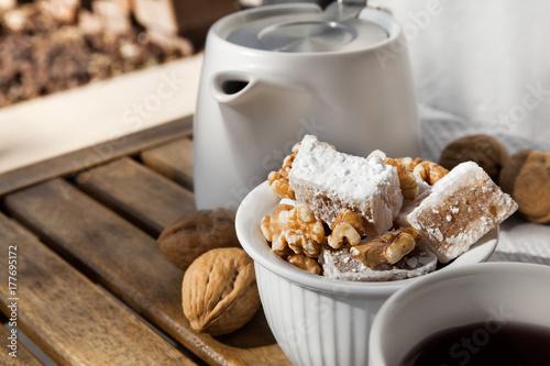 Zdjęcie XXL Turecki deser Lukum z orzechami włoskimi skonfigurować na drewnianym stole do przerwy na herbatę