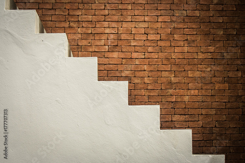 Valokuva  Side view of white empty stairs with brown brick wall background in vintage style