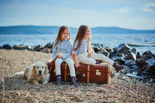 Photo  Two little twin sisters on a walk with dog on the beach.