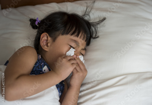 Obraz na plátne Little girl with cold blowing her runny nose in bed