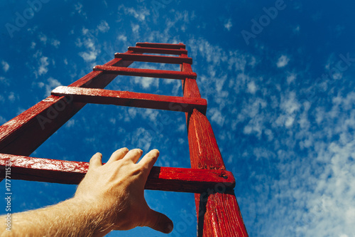 Fotografiet  Hand Of Man Reaching For Red Ladder Leading To A Blue Sky