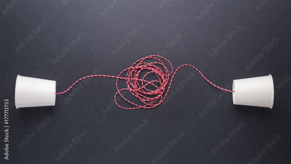 Fototapeta Two white paper cup connect with red rope used for classic phone on black stone table board. For old communication system concept