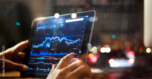 Businessman checking stock market data on tablet on night background Canvas-taulu