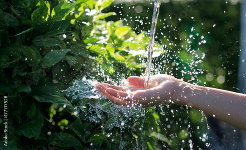 Spoed Foto op Canvas Natuur Water pouring in woman hand on nature background, environment issues