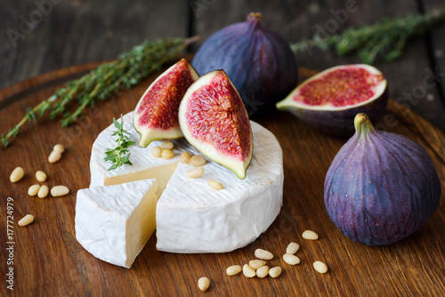 Camembert cheese with fresh purple figs, thyme and pine nuts on cutting board