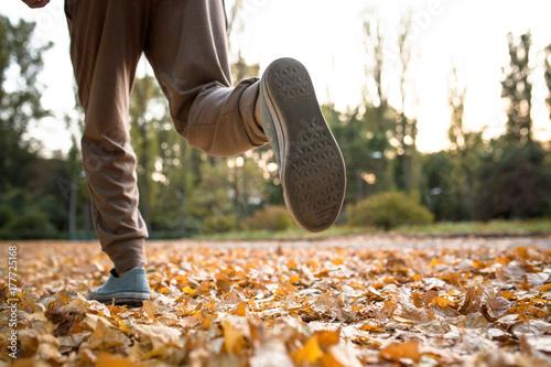 Zdjęcie XXL Zamyka w górę widoku mężczyzna bieg na wysuszonych jesień liściach. Zdrowy styl życia, mężczyzna jogging na zewnątrz.