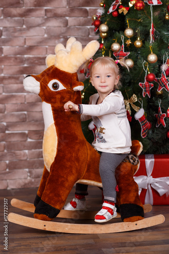 138c8348199e0 Christmas beautiful cute baby girl posing in casual clothes close to new  year pine green tree