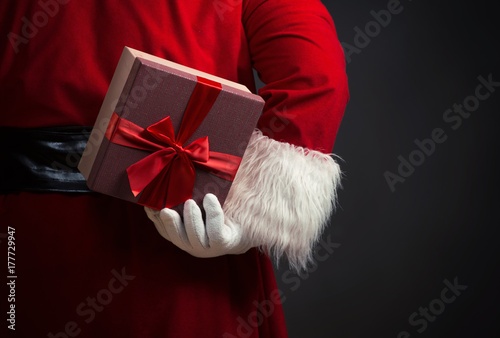 Zdjęcie XXL Święty Mikołaj trzyma teraźniejszość nad ciemnym tłem ,.