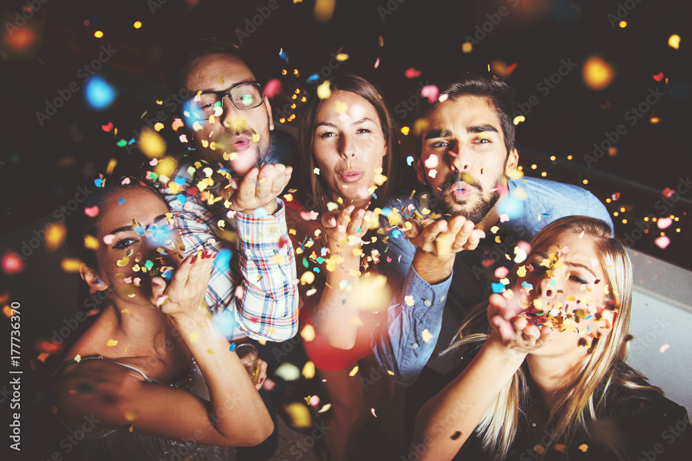 Fototapeta Group of people having a party, blowing confetti
