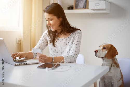 Woman using laptop and credit card for on-line shopping while sitting at home office Poster