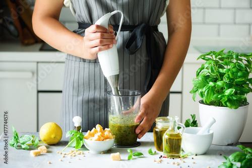 Photo  Woman using hand blender to make pesto