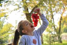 Little Girl Eats Grape In Park...