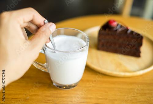 Fototapeta Ręka trzyma szkło mleko z czekoladowymi tortami na odgórnym czerwonym czereśniowym tle w drewnianym talerzu na drewno stole