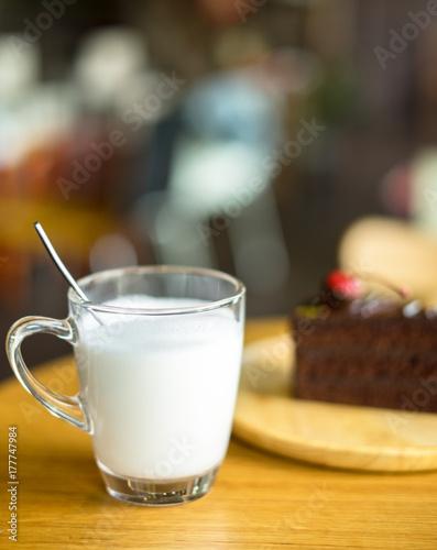 Fototapeta szklanka mleka z ciasta czekoladowego na wierzchu czerwony wiśni tle w drewnianej tablicy na stół z drewna
