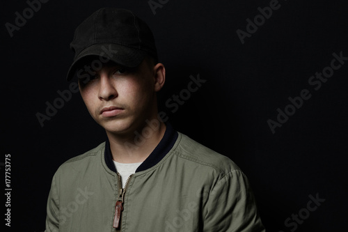 Stampa su Tela teen boy posing with black cap and bomber jacket in front of black background