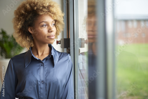 Laughing young afro-american woman standing at window at home Canvas Print