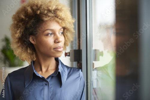 Laughing young afro-american woman standing at window at home Wallpaper Mural