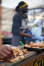 Chicken And Sausage On A Grill African Man On The Background In Camden